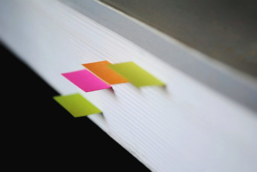 Picture of a book profile with 4 different colored bookmarks