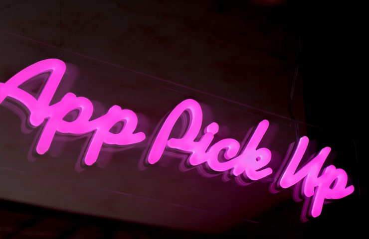"Picture with neon light saying ""App Pick Up"""